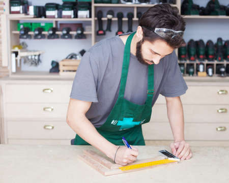 Carpenter, bearded hipster in working clothes, T-shirt and a green apron and safety glasses in the studio working with tools Stockfoto