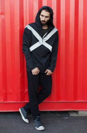 Mens youth street fashion. A man is posing in a black jacket of new technological materials on the street, on a red background. Windbreaker
