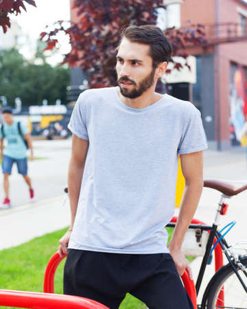 City fashion. A bearded hipster man in a fashionable gray T-shirt, black pants posing with a tricycle bike in the city park on a summer day.