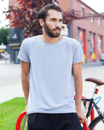 Youth fashion. A bearded hipster man in a fashionable gray T-shirt, black pants posing with a tricycle bike in the city park on a summer day.