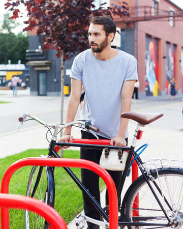 Portrait. A bearded hipster man in a gray T-shirt, black pants posing with a tricycle bike in the city park in the afternoon. 写真素材