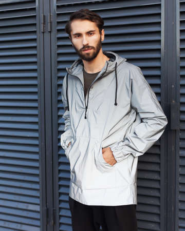Modern materials in the fashion industry. Mens youth street fashion. Windbreaker from the rain. A man is posing in a fashionable silver jacket made of new technological materials.