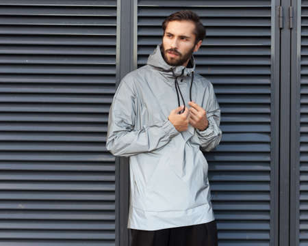 Modern materials in the fashion industry. Windbreaker from the rain. A man is posing in a fashionable silvery waterproof jacket made of new technological materials.