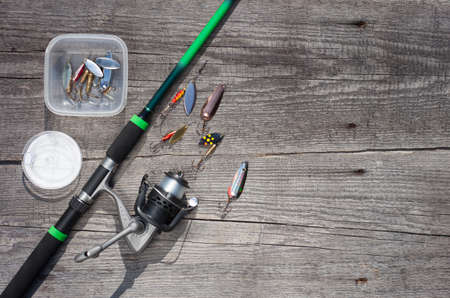 Fishing rod and spinning reel with line on gray wooden background with free space, Top view.