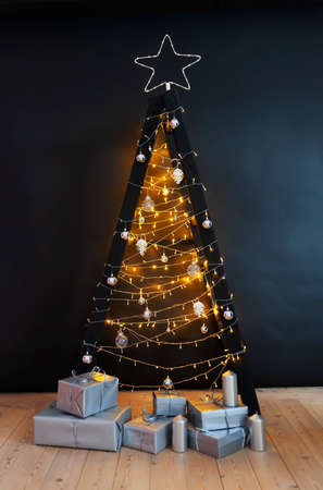 Scandinavian style Christmas tree. Made of a step ladder and decorated with lights and garlands on black background. 版權商用圖片