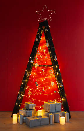 Scandinavian style Christmas tree. Made of a step ladder and decorated with lights and garlands on red background. 版權商用圖片