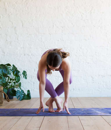 Beautiful young woman working out in loft interior, doing yoga exercise on blue mat