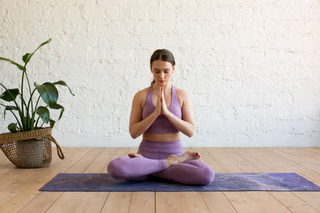 Young attractive sporty woman practicing yoga, doing Ardha Padmasana exercise, meditating in Half Lotus pose with namaste, working out, wearing sportswear, indoor full length, yoga studio