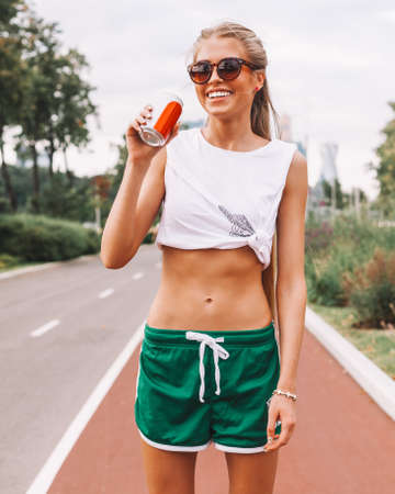 Beautiful sexy blonde poses in a white top, yellow golf and green shorts, sunglasses enjoys a drink in the can. Sports park. Warm summer evening. Outdoor.