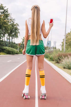 Beautiful sexy blonde with long hair posing in a white top, yellow golf and green shorts on vintage roller skates. Rear view, back. Sports park. Warm summer evening.