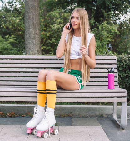 Very Beautiful young woman with long hair in vintage roller skates, green shorts and a white top is talking on a smartphone, sitting on a bench. Summer evening on the street of a European city.