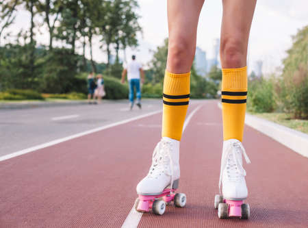 Part of the body, long hard legs on vintage roller skates in bright yellow golfs on a warm summer evening in the park. Banque d'images