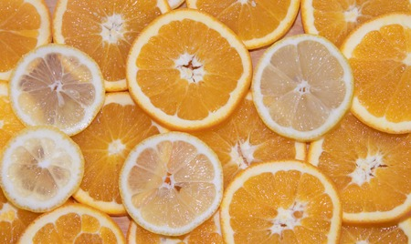 Sliced orange and lemon on a board isolated on white background. Fruits on the board. Fruits on a white background. Cutting fruit. Sliced fruit Stock Photo