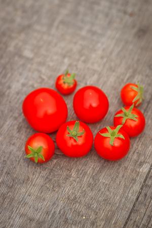 Cherry tomatoes on a wooden background. Autumn harvesting. Stock Photo