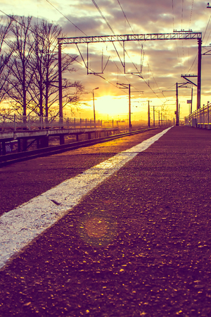 The Russian railway at sunset in the spring. Travel by transport. Transportation of passengers. Rails and sleepers