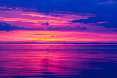 A bright sunset on the Gulf of Finland. Sunset at the sea. Sunset on the Gulf. warm summer, crimson sky and small waves