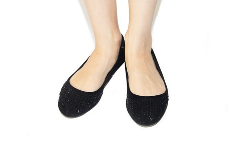 Black ballet flats on female legs on a white background. Women's shoes. Women's summer footwear. Business black ballet shoes on a white background. Shoes without a heel. Comfortable casual shoes