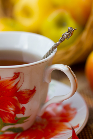 A cup of tea and apples with maple leaves. Autumn tea party, autumn mood, seasonal postcard.