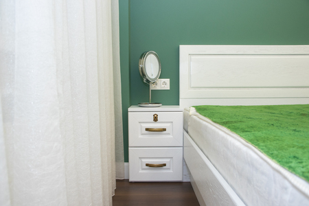 Large white bed in the bedroom. The interior of the bedroom. White green bedroom 免版税图像