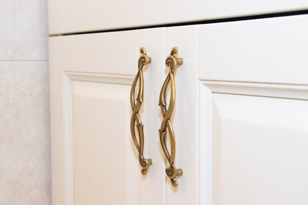 Dark handle on the white facade of the cabinet. Furniture fittings. Open and close the cabinet. Banque d'images