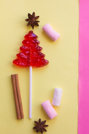 Lollipop on a gentle background. Christmas candy and caramel sticks on pink and yellow backgrounds 免版税图像