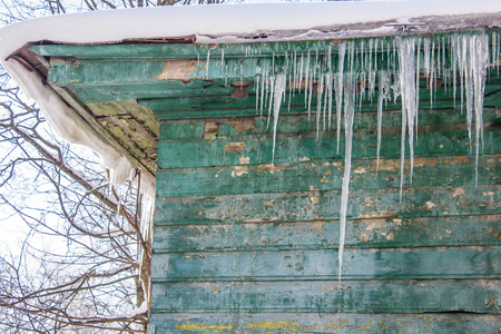 icicles hang from the roof of houses. frozen water. water aggregation