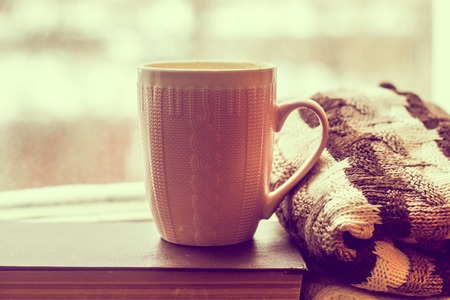 Coffee and a sweater on the book by the window. bad mood. relax Stockfoto