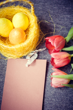 Easter card. Painted eggs in a basket and flowers in a vase. Orthodox holiday. Religion and culture