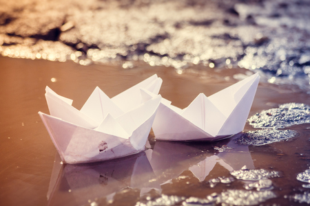 The paper boat floats through the spring puddles. Children's entertainment. Paper origami