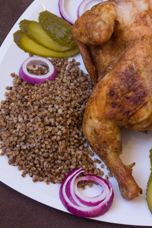 Baked in seasonings chicken with buckwheat. Home kitchen. Baked chicken carcass. Chicken with buckwheat, onions and cucumbers