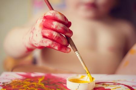 De jongen schildert op papier. Rode en gele verf. Activiteiten voor kinderen. De hobby van kinderen. Tekening