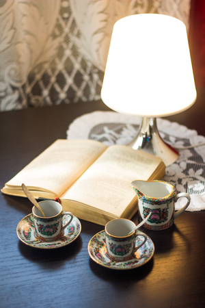 Cups with coffee on a table with a lamp and a book. Cups of coffee. Hot drink. Spiritual gatherings. Stockfoto