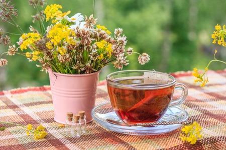 Sommertee mit einem Buch auf der Terrasse. Sommertee mit Blumenstrauß. Tasse mit Tee, Blumen, Buch, Balkon
