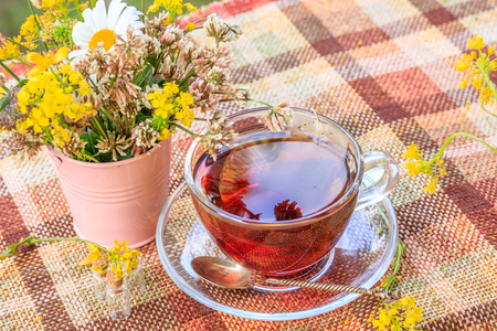 Summer tea with a book on the terrace. Summer tea with a bouquet of flowers. Cup with tea, flowers, book, balcony