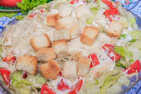 Caesar salad plate. Festive Salad. Greek salad . Delicious salad with chicken and crackers Фото со стока