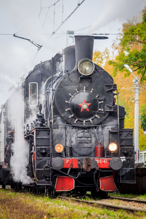 Old Russian locomotive on the railway. Old black locomotive. Smoke from the engine. Russian railway. Locomotive. Russia, Leningrad region October 7, 2018