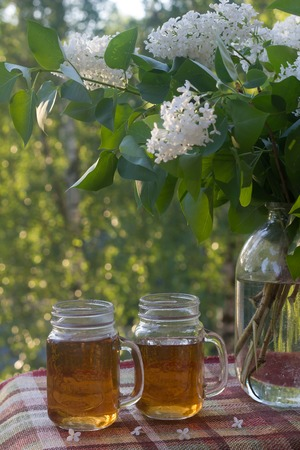 Cold drink tea black in glasses. Tea on the balcony. Tea for Two. Cold drink. Bouquet of flowers . Flowers and tea