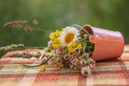 Bouquet of wild flowers in an iron bucket. Beautiful summer wildflowers. Flowers in a bucket