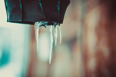 dripping icicles. water ice icicles hang from an iron beam