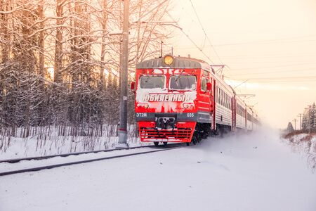 Russian train in the winter. The train rides by rail in the winter in the woods. Winter forest. Public transport. Russia Leningrad region, Gatchina district January 6, 2019