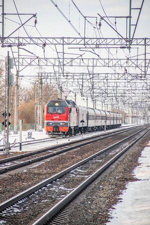 Russischer Zug. Lokomotive mit Autos. Personenzug. Öffentlicher Verkehr. Russland Metallostroy 8. März 2019 Editorial
