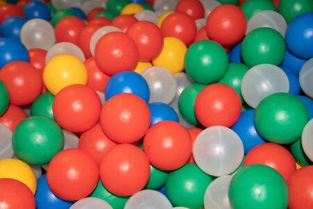 Bälle für einen trockenen Poolhintergrund. Hintergrund vieler farbiger Plastikbälle. Baby Delight Bunte Bälle. Kugeln aus Kunststoff. Trockenbecken Standard-Bild