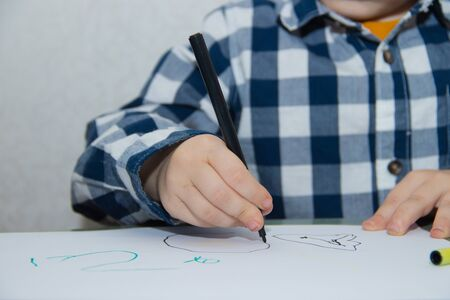 The boy draws felt-tip pens on paper. Drawing. Little boy. Children's drawing. Developmental activities. Colored markers
