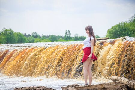 The girl at the waterfall. Young beautiful girl on a little waterfall. Little waterfall. Banque d'images