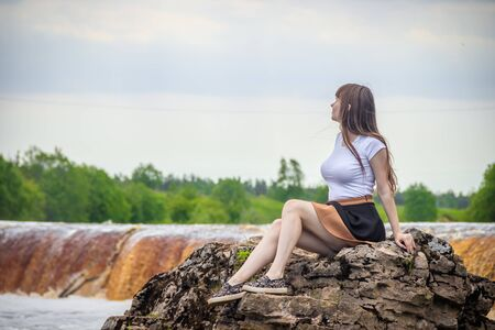 The girl at the waterfall. Young beautiful girl on a little waterfall. Little waterfall. Standard-Bild