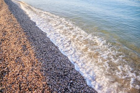 Sea wave in the morning light. Sea wave and beach. Sea wave background. Crimea. Wave and pebble beach. Rest and travel to the sea. Dawn 免版税图像