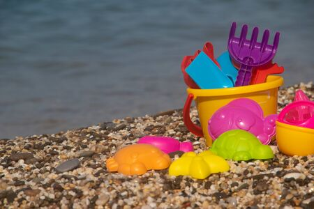 Plastic children's toys for sand on the background of the sea. Kids toys. Plastic sand toys. Bright toys. Sand construction. Children's activities. Hobbies and recreation. Background toys on the beach