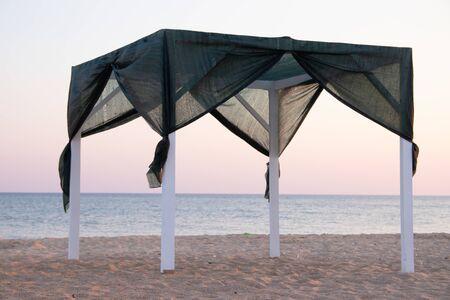 Pavillon am Strand am Meer. Sandstrand. Vorhänge entwickeln sich im Wind. Abendlicht