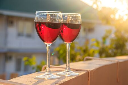 Two glasses of red wine are backlit by the sun. Grape drink. Home wine.