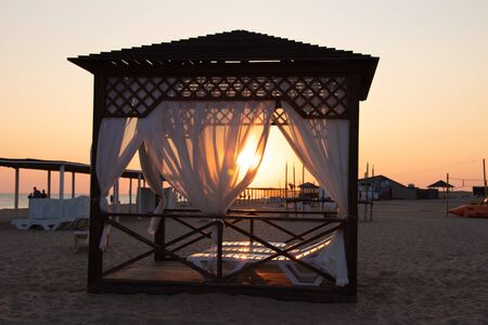 Gazebo on the beach by the sea. Sand beach. Curtains develop in the wind. Evening light